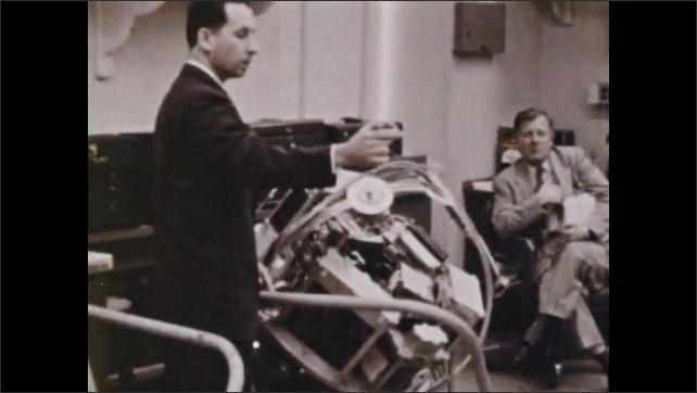 1960s: UNITED STATES: study into space wreckage. Men investigate physical phenomenon. Hand looks through debris