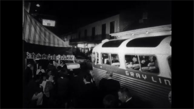 1960s: People walk down busy street at night in New Orleans. Bus full of people drives down crowded street. Marquee sign for Crystal Belle. Sign for Sextana. Sign for Tempeste and Storm.