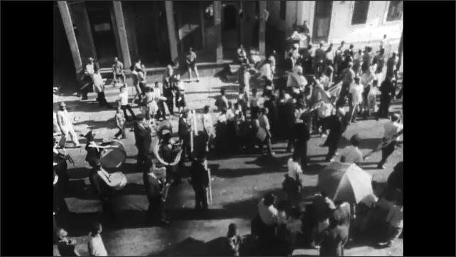 1960s: Marching band plays music while marching down street. People sit inside church for funeral. Open casket sits at the head of sanctuary.