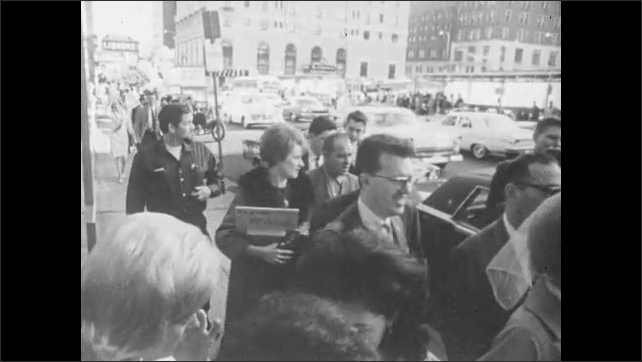 1960s: View of tall building, then busy city streets with many people walking and cars driving. View of brick building.