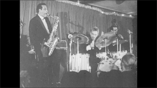 1960s: Gene Krupa drums frantically. Jazz trio play instruments on stage for audience. Man strikes drum cymbals. Hands play piano.