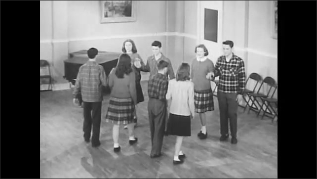 1950s: Male and female dancers perform the do-si-do.  Four couples stand together to form a square.  Couples demonstrate dance steps.  Partners dance in circles.