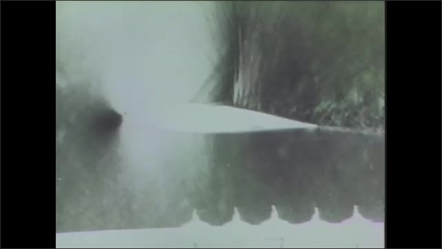 1970s: UNITED STATES: Cross section of wing in wind tunnel test. Shock waves around wing in test. Curved wing.