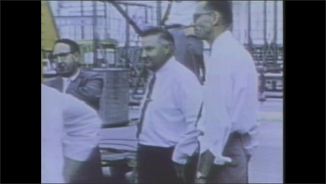 1970s: UNITED STATES: men gather around plane. Men design new plane.