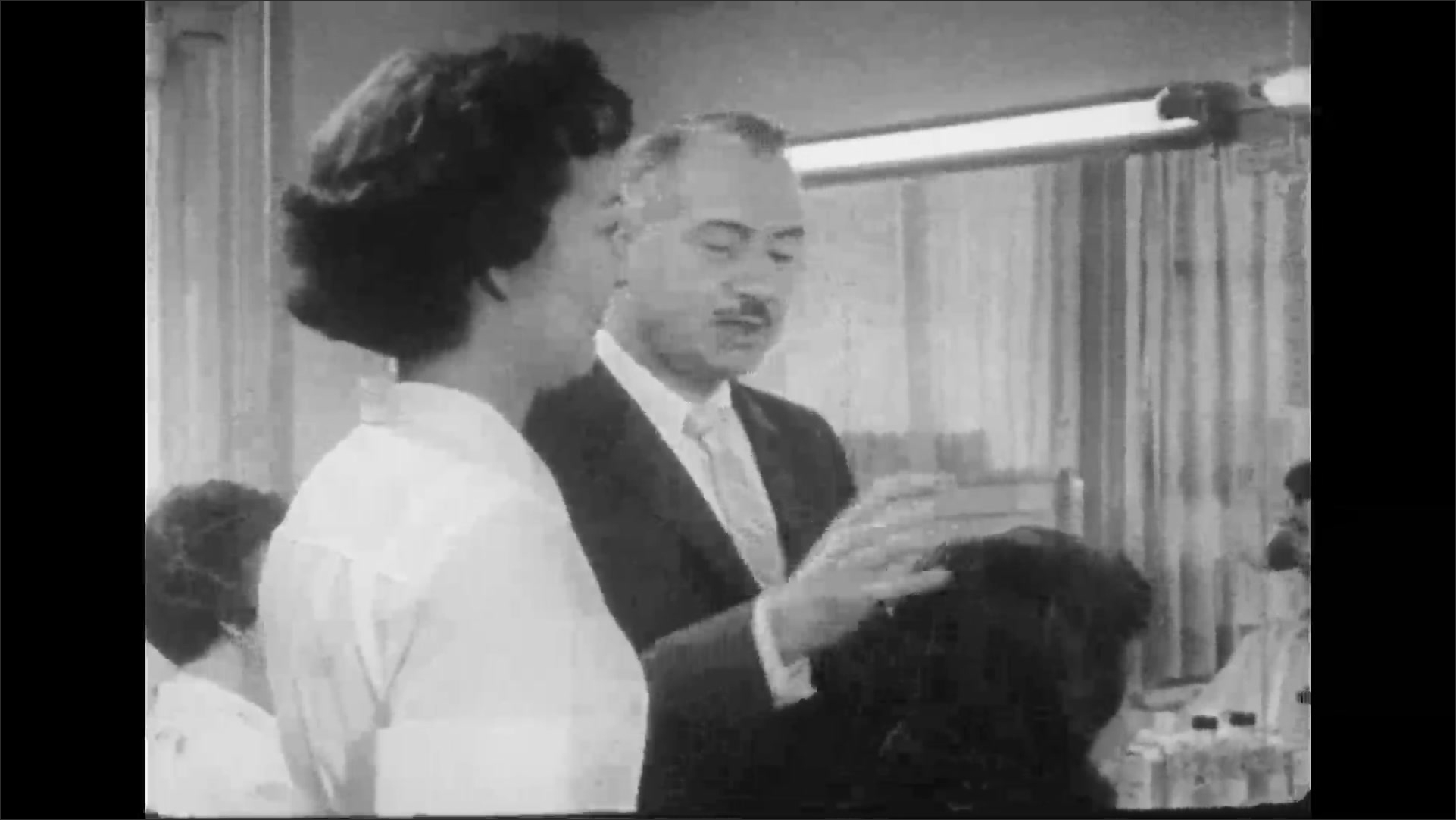 UNITED STATES 1950s: Man walks woman through salon / Man with woman in chair / Man touches woman's hair, stylist walks to chair / Man talks to stylist / Man moves to next woman.