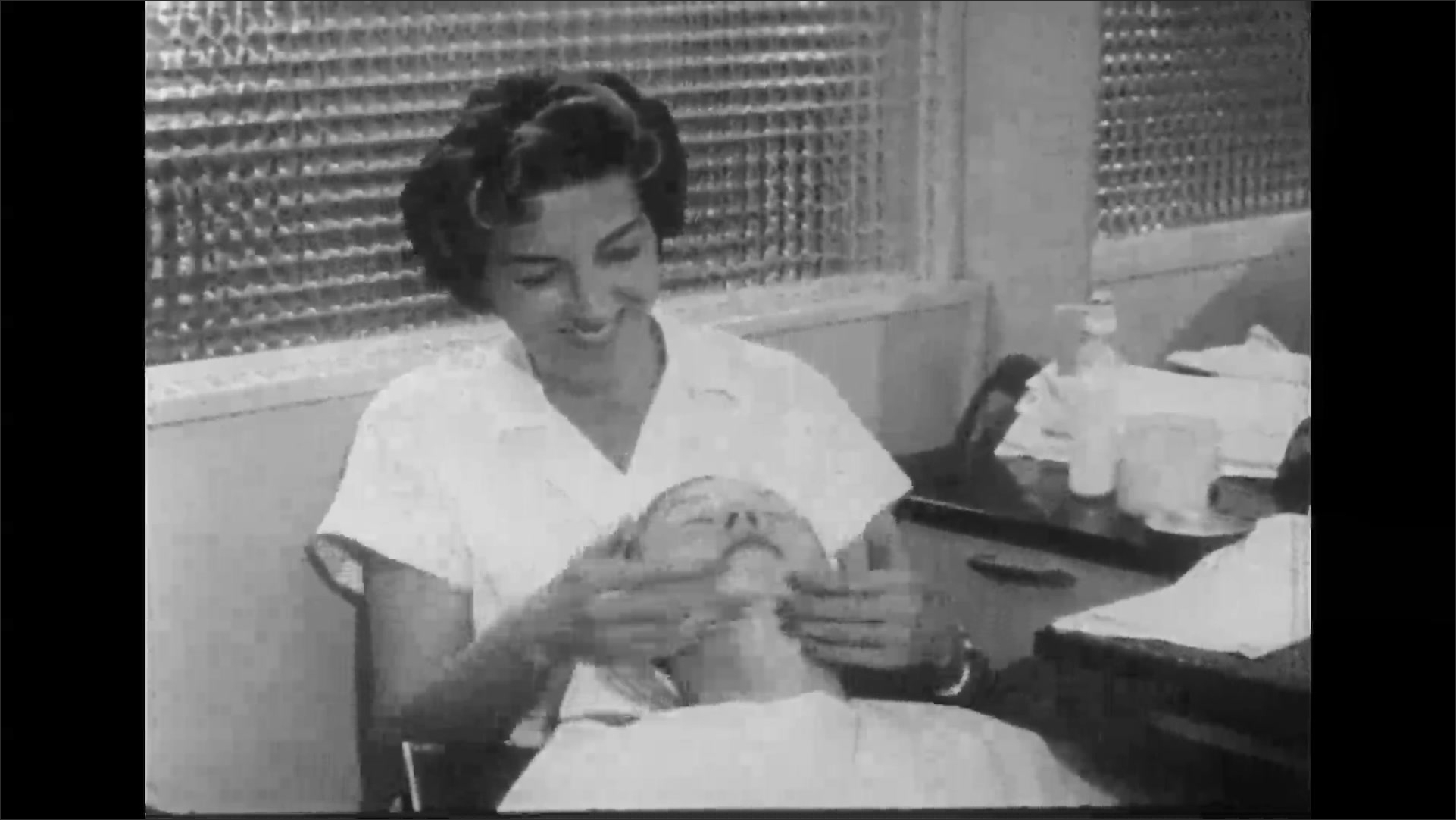 UNITED STATES 1950s: Stylist gives woman facial / Close up of stylist.