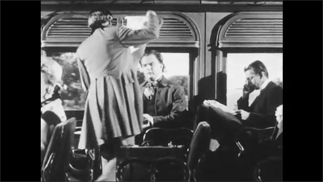 1940s: Passengers in train car. Man speaks to man seated in train car. Man unrolls scroll and shows it to man.