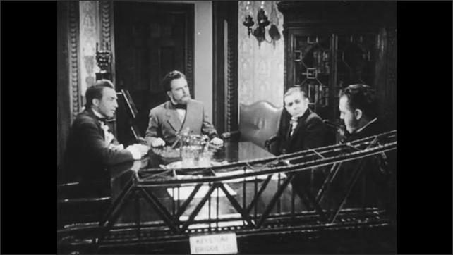 1940s: Man talks. Men seated at table speak.