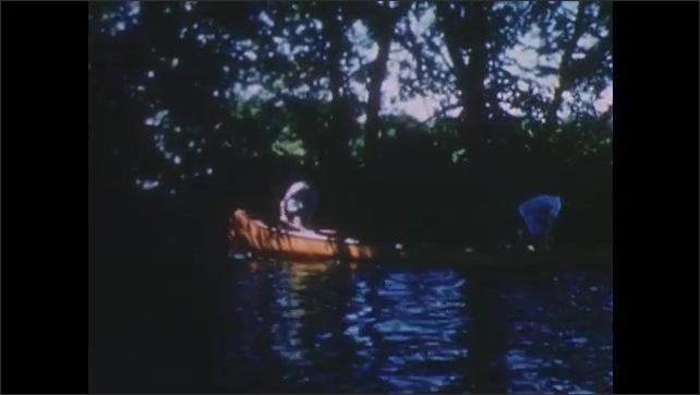 1950s: UNITED STATES: view across pond in summer. Boys on boat on river. Boys paddle canoe along river in summer