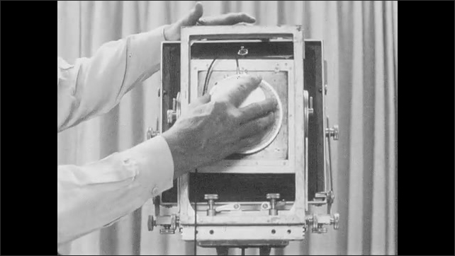 1950s: Photographic plates lie in a case. Hands place lens cap on camera and remove it from tripod.