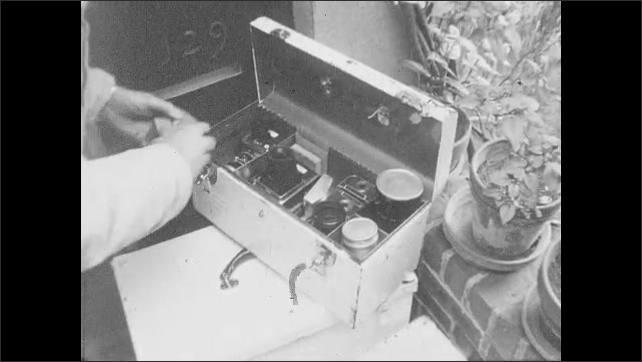 1950s: Man packs lenses and camera into carrying case. Hands open and check the contents of small camera case. Hands lift carrying cases and walk away.