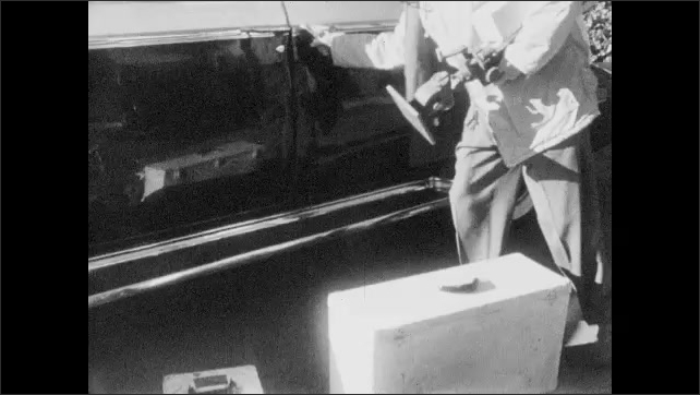 1950s: Man opens case and checks exposure meter inside. Man closes meter case. Man opens car door and loads camera cases and tripod into back seat.