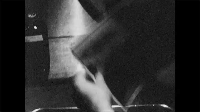 1950s: Hands move photographic image around in rinse tray. Hands remove final image and point to areas of shadow and light.