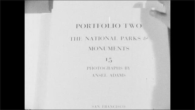 1950s: Bound portfolio sits on tale. Hands untie binding and open photographic portfolio. Hands slide pages of portfolio to side. Photograph of pine trees.