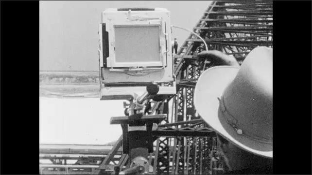 1950s: Ansel Adams inserts film plate into camera and takes photo of bulldozer. Metal scaffolding.