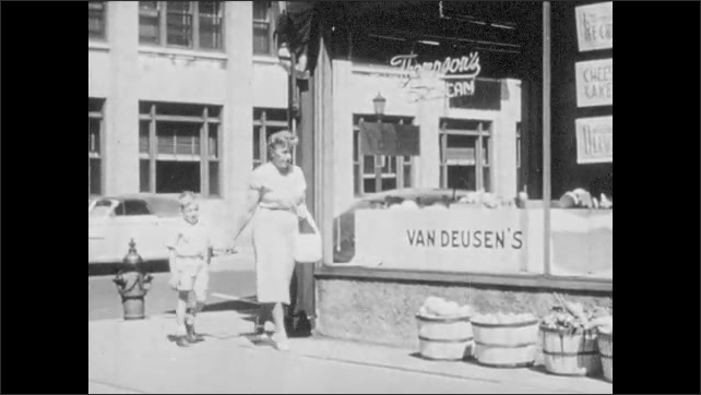 1950s: Little boy walks reluctantly hand in hand with woman. Woman and boy turn corner and woman examines produce in front of store. Policeman appears and little boy tries to hide behind woman.