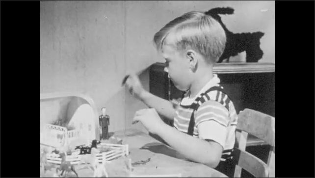 1950s: Boy does imaginative play with farm and house figures on his play table.