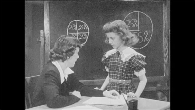 1950s: Teacher talks with girl and hands her  paper. Girl leaves desk.