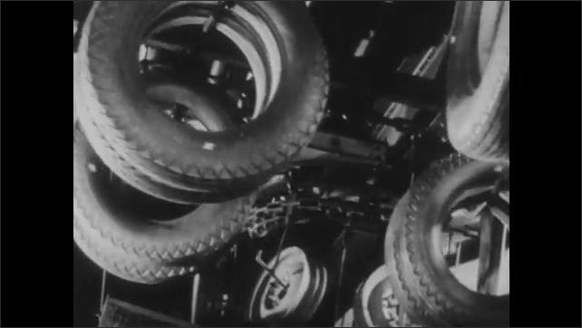 1940s: UNITED STATES: engine fitted into car on production line. Tires at car factory. Body lifted onto new car on production line