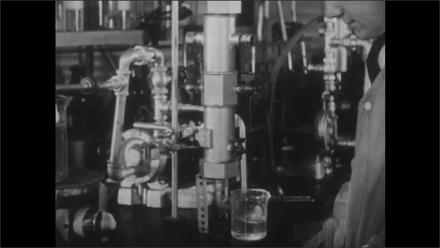 1940s: UNITED STATES: scientist pours solution from glass beaker. Water drop and leak testing.
