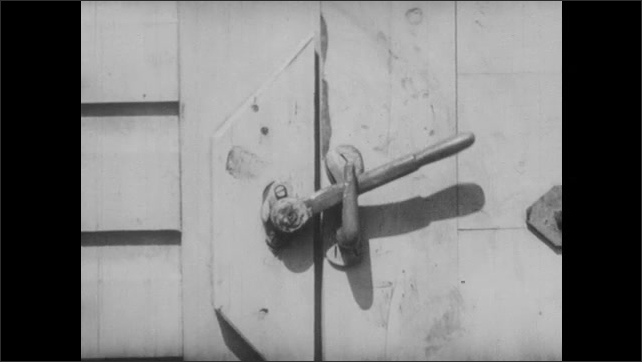 1940s: UNITED STATES: man in research suit. Latch closes on freezing room door. Scientist wears aviation suit in room.