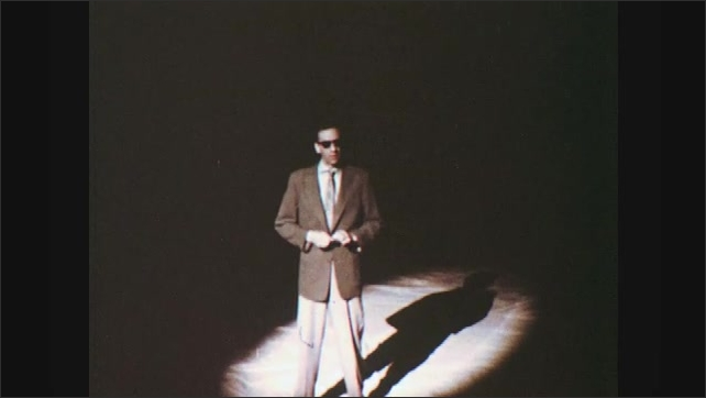 1960s: Blind man stands in spotlight and speaks.  Man twists object in hands.