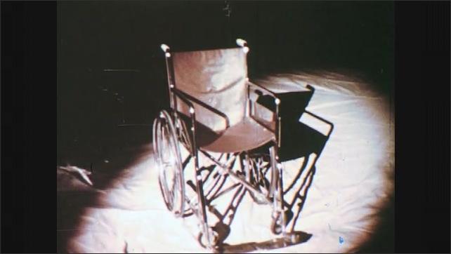1960s: Wheelchair in spotlight.  Shadow of man.