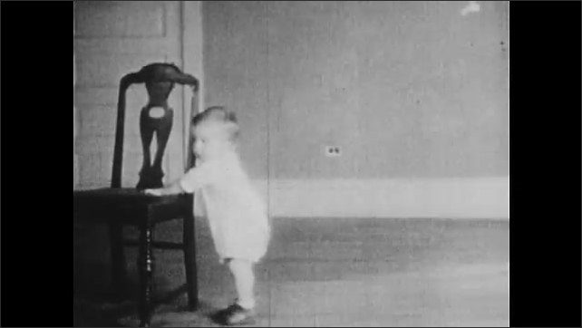 1930s: Child moves chair in room to under string hanging from ceiling with cookie attached to it. Child climbs on chair and grabs cookie. Child moves chair.