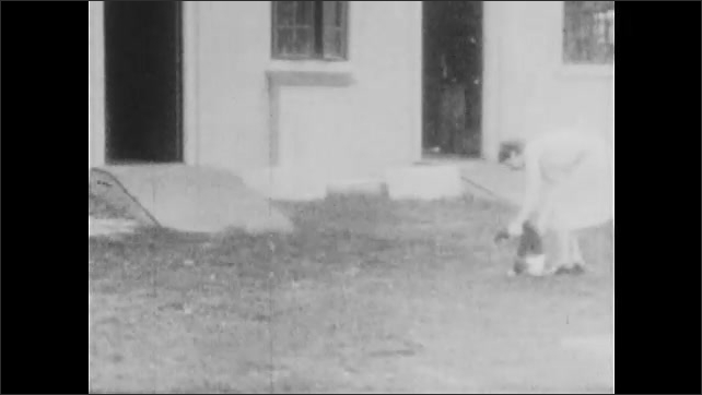 1930s: UNITED STATES: ramps and doors of building. Lady with chimp outdoors. Chimp runs to man