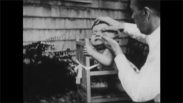 1930s: UNITED STATES: man spins baby on chair. Baby cries on chair. Man puts hand on baby's face