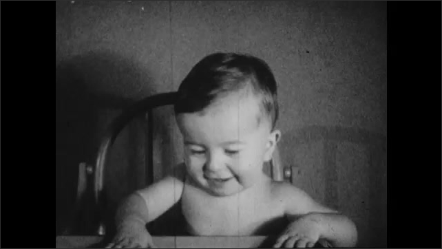 1930s: Text placard. Baby sits in highchair and smiles.