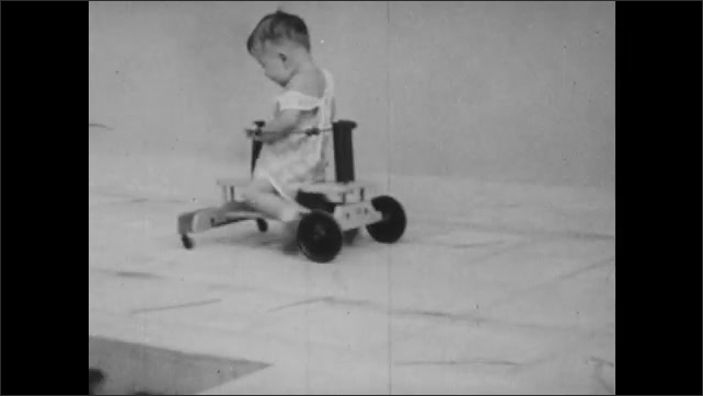 1930s: Text placard. Baby propels himself across ground in wooden scooter. Woman watches baby push itself across ground on scooter