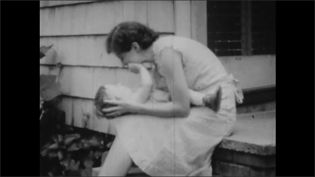 1930s: Man holds and kisses baby chimpanzee. Text placard. Woman holds human baby in lap and speaks. Human baby touches woman's face.