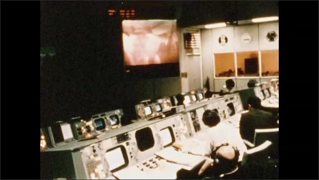 1960s: Men sit in mission control room looking at screen broadcasting from Apollo 13 on its way to moon.