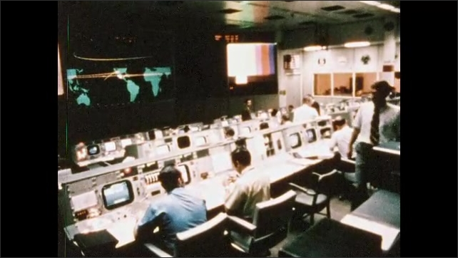 1960s: Broadcast screen goes blank. Men sit at consoles in NASA mission control room. Man is looking at book. Man writing in book. Man looks around.