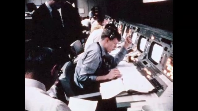 1960s: Flight director's seat in NASA mission control room. Man writing in binder. Man in front of monitor. Men in row at console. Man in headset. Man in headset talking. Men in front of monitors.