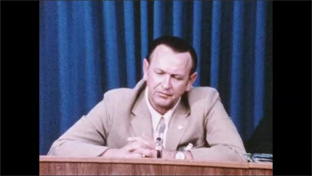 1960s: Man podium is talking into microphone at press conference.