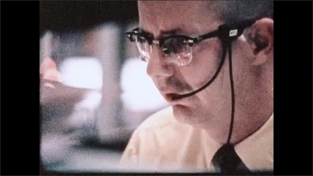 1960s: Man wearing headset in NASA mission control room shakes his head. Man talk in mission control. Man wearing headset. Man at monitor. Man looks in binder.