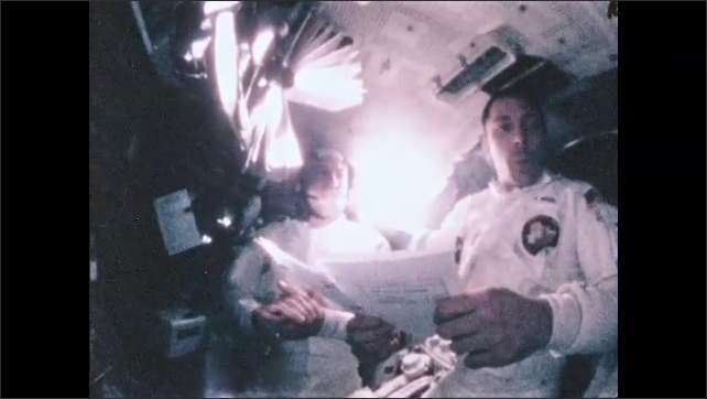 1960s: Men talking in group in NASA mission control room. Man points at monitor. Astronauts in capsule of Apollo 13 in space, looking at document.