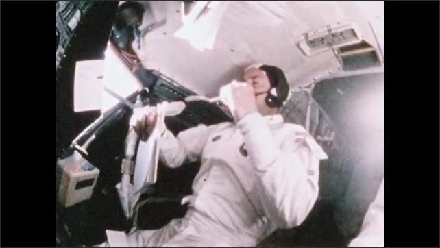 1970s: Astronaut Fred Haise Jim Lovell sleeps in spacecraft. Astronaut looks at watch, wipes face.