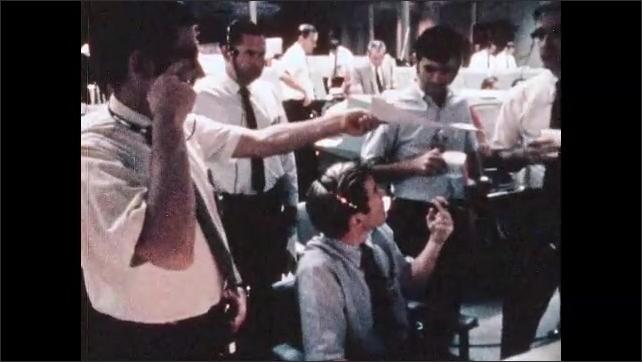 1970s: Men at mission control talk, work, look at monitors, sit at consoles.