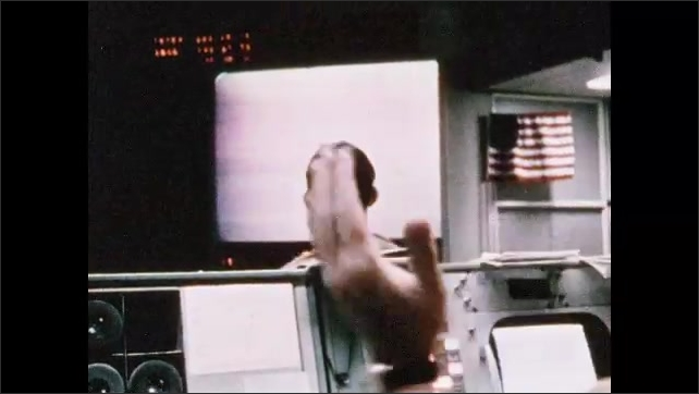 1970s: Men at command center sit at consoles, watch monitors, write, talk to astronauts, clap. Spacecraft parachutes down. People in the street watch tv, smile.