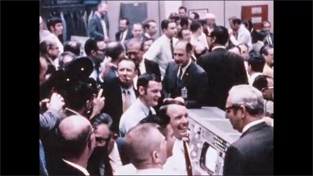 1970s: Men at mission control congratulate one another, shake hands, cheer. Astronauts walk across aircraft carrier. Astronauts sit in robes, listen on phone.