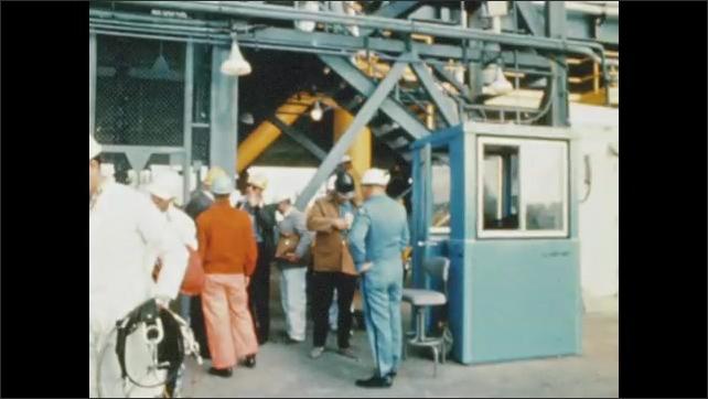 1970s: UNITED STATES: Spacecraft on gantry. Men walk down steps by rocket. Astronaut walks down steps. Monitors watch rocket.