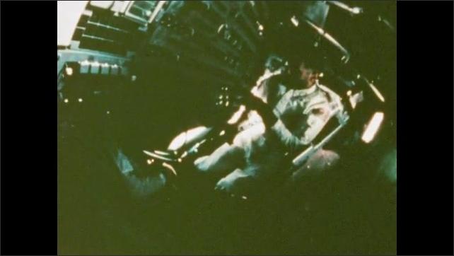 1970s: UNITED STATES: crew inside Apollo 8 do routine checks. Mission control workers check data