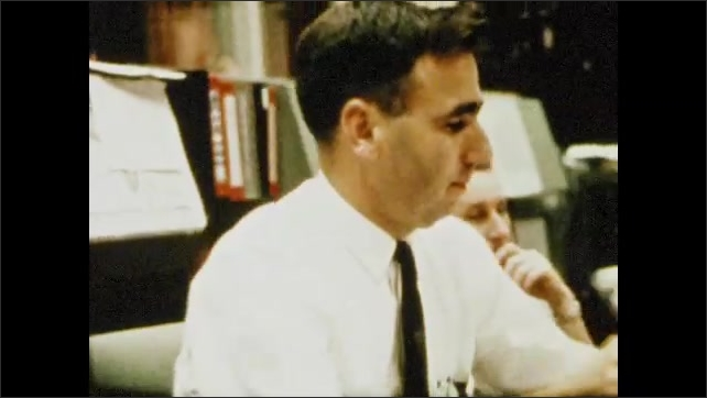 1970s: UNITED STATES: flight controller puts in call to Apollo 8. Man sighs with relief. Footage of landed Apollo 8.