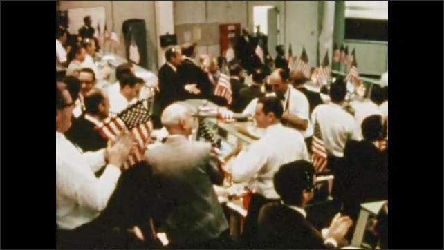 1970s: UNITED STATES: celebrations in mission control. American flag and banners at Houston mission control. Roaring and applauding at mission control. Man with cigar celebrates