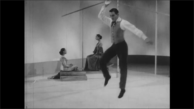 1950s: Man standing still near fence begins dancing around as women sit still in different poses.