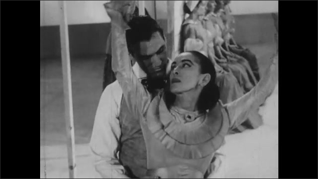 1950s: Man and woman dance as women and man stand still in poses. Dancing man and woman embrace, holding arms. Man on platform walks forward off platform.