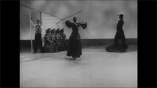 1950s: Woman begins dancing as man in hat stands on platform and four women sit against wall. Man watches.